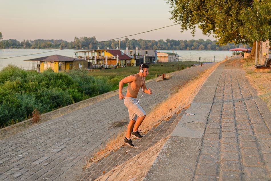 Młody mężczyzna wbiega po schodach nad rzeką